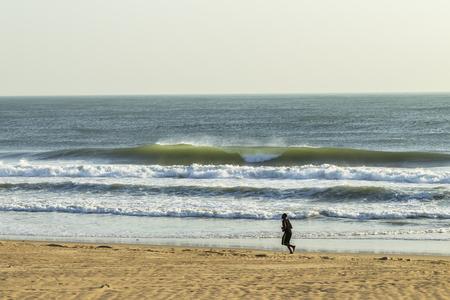 alongside: African man run on beach sands alongside ocean crashing waves.