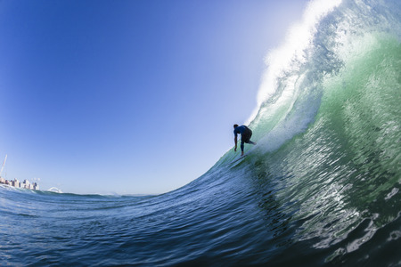 Surfing surfer riding ocean wave swimming water rear action.