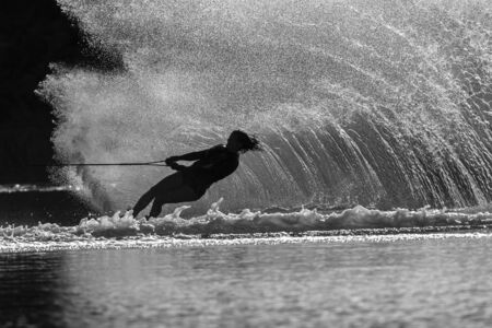water skiing: Water skiing girl hard turn action silhouetted black white contrasts