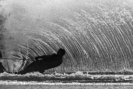 water skiing: Water skiing athlete hard turn action silhouetted black white contrasts Stock Photo