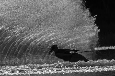 Water skiing girl hard turn action silhouetted black white contrasts