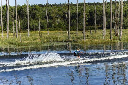waterskiing: Young teen girl water-skiing on rural mountain lake waters during summer season. Stock Photo