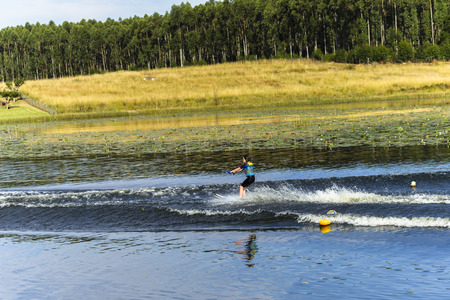 waterskiing: Young girl water-skiing on rural mountain lake waters during summer season. Stock Photo
