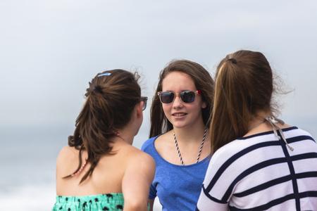 socializando: Chicas adolescentes hablando de socializaci�n en las vacaciones de verano en la playa. Foto de archivo