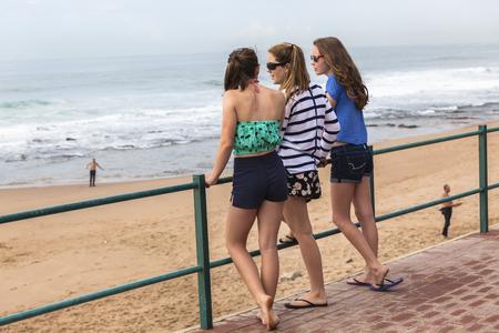 socializando: Chicas adolescentes hablando de socialización en las vacaciones de verano en la playa. Foto de archivo