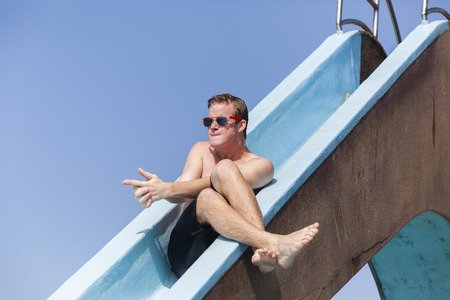 jokes: Boy teen on pool slide summer acting jokes fun. Stock Photo