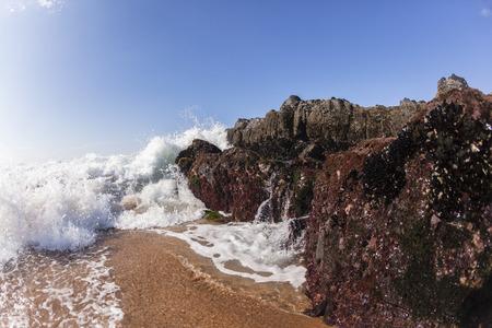 Ocean wave shore break crashing sea water into rocks along beach Stock Photo