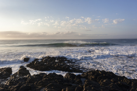 swells: Ocean wave swells crashing front of rocky coastline
