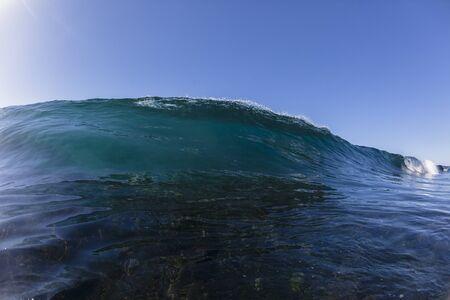 swells: Ocean wave hollow crashing blue water swimming closeup.