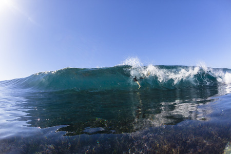 Surfer surfing escapes danger on reef shallow ocean wave swimming closeup.