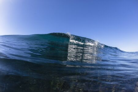 swells: Blue wave water swimming closeup.