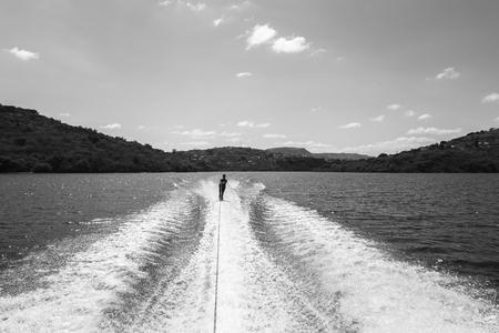 waterskiing: Waterskiing teenager on dam waters in black white landscape