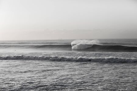 swells: Ocean wave swells crashing along coastline black and white vintage Stock Photo