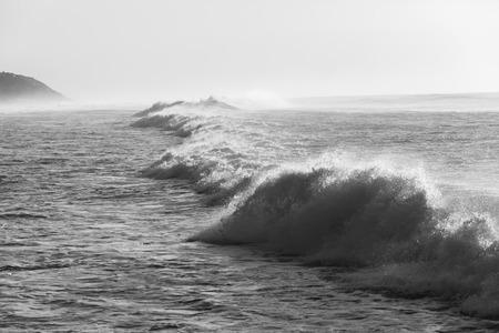 swells: Ocean waves crashing water power in black and white along beach coastline