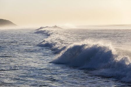 crashing: Ocean wave waters crashing along beach coastline Stock Photo