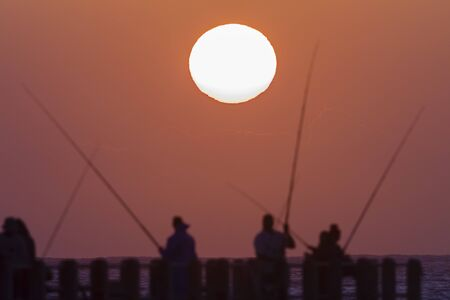 silhouetted: Sunrise  fishermen on beach pier silhouetted