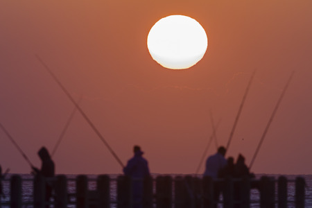 silhouetted: Dawn Sunrise  fishermen on beach pier silhouetted Stock Photo