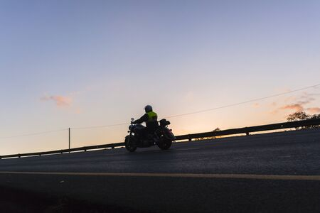 silhouetted: Biker and motor bike on the road dawn light silhouetted