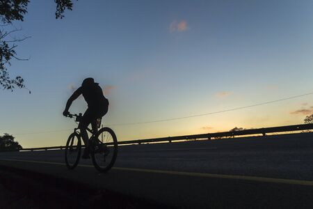 Cycling Unidentified silhouetted dawn on road