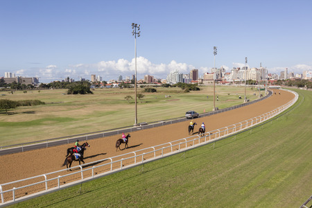 jockey's: Race Horses Jockeys to starting gates for race overlooking track around Royal Durban golf course landscape South Africa.