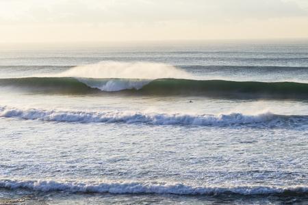 swells: Ocean wave swells crashing beach coastline early morning Stock Photo