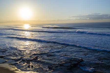 swells: Ocean wave swells moving towards beach coastline early morning