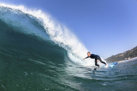 Surfing surfer inside riding focus closeup blue hollow wave swimming photo of water action