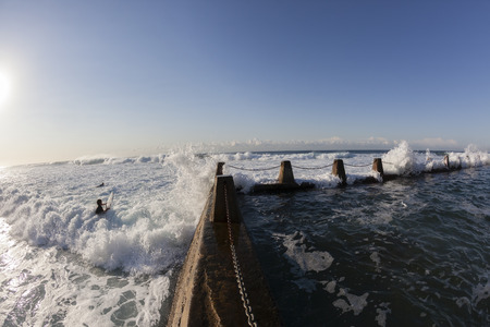 surfers: Surfing surfers paddling  hard ocean entry next to tidal pool crashing waves Stock Photo