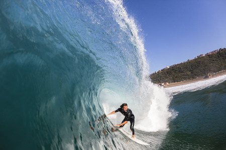 Surfing surfer rides inside blue large hollow crashing ocean wave a swimming water photo closeup of action.