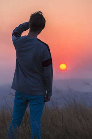contryside: Young man watching sun going down at sunset over the landscape at days end.