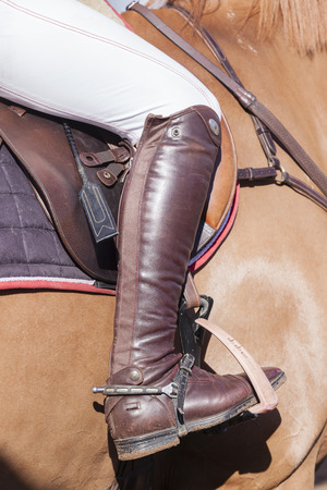 horse show: Horse show jumping rider leg boot saddle leather details closeup