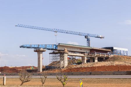 infraestructura: Gr�a de construcci�n de la carretera nueva entre secci�n transversal sobre rampas de columnas de hormig�n por encima de las carreteras