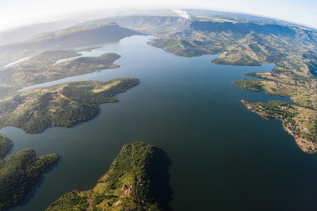 Aerial flying birds eye view of Inanda Dam waters valley and hills with tribal habitat homes landscape outside Durban Stock Photo