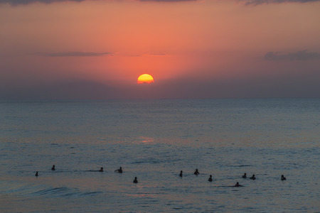 surfers: Surfing surfers silhouetted ocean waters early dawn sunrise horizon landscape.