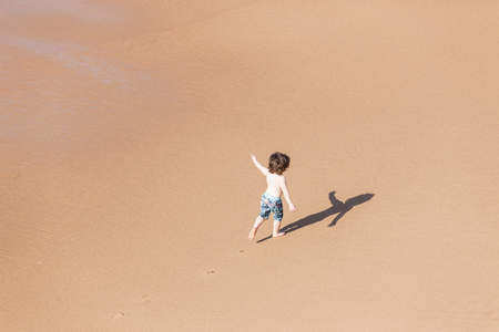 playtime: Young boy child on beach ocean sands new playtime explore adventure overhead photo.