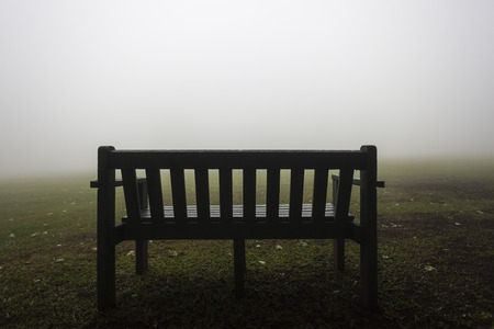 contrasted: Bench chair edge of sports field covered in cloud mist contrasted