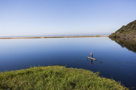 paddler: Paddler on sup board paddling across blue lagoon glassy smooth water scenic landscape. Stock Photo