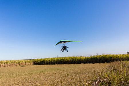 rural countryside: Flying microlight plane pilot landing on rural countryside grass airstrip