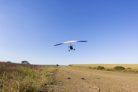 piste atterissage: Flying microlight aircraft  pilot passenger take off  on rural countryside grass airstrip