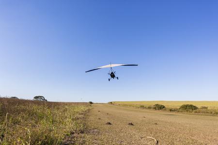 airstrip: Flying microlight aircraft  pilot passenger take off  on rural countryside grass airstrip