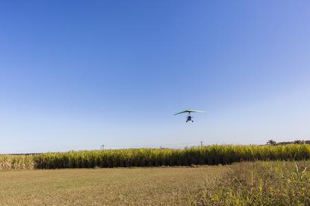 airstrip: Flying microlight plane pilot  landing on rural countryside grass airstrip Stock Photo
