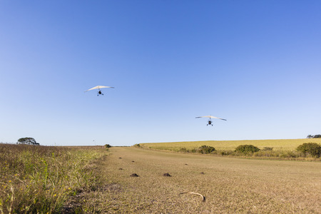 airstrip: Flying microlight planes pilots passengers take off and landing on rural countryside grass airstrip