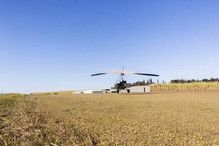 piste atterissage: Flying microlight  plane pilot passenger landing on rural countryside grass airstrip