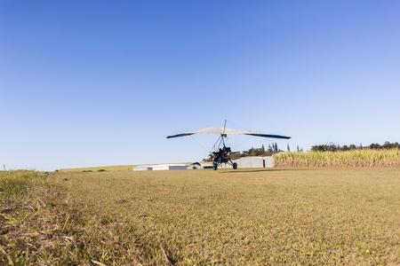 rural countryside: Flying microlight  plane pilot passenger landing on rural countryside grass airstrip