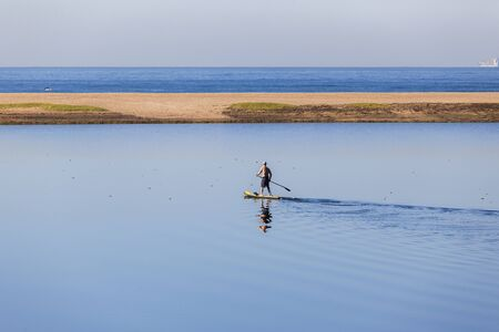 paddler: SUP Paddler on beach blue lagoon glassy smooth water scenic landscape.