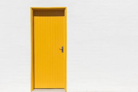 Amarillo entrada de la puerta pintada en edificio blanco pared exterior detalle