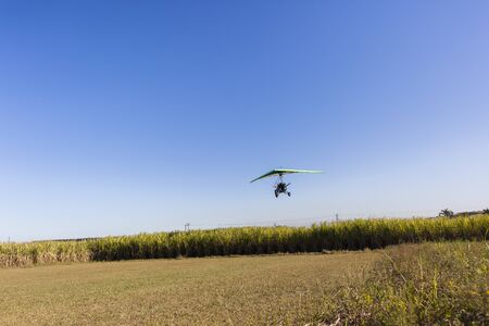piste atterissage: Flying microlight plane pilot passenger landing on rural countryside farm grass airstrip Banque d'images