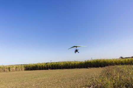 airstrip: Flying microlight plane pilot passenger landing on rural countryside farm grass airstrip Stock Photo
