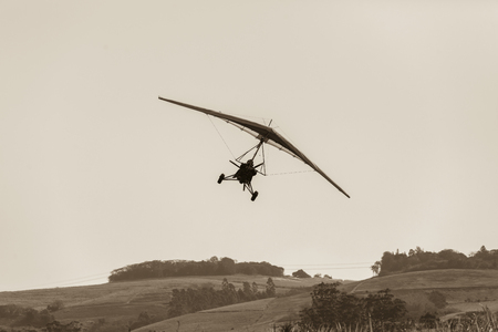 airstrip: Flying microlight plane pilot landing approach on rural countryside grass airstrip