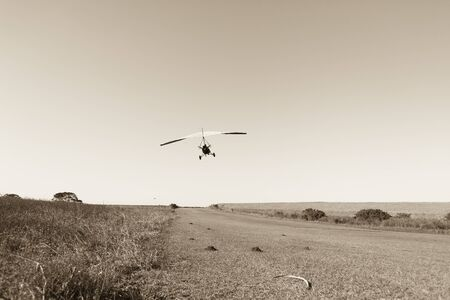 airstrip: Flying microlight plane pilot take off on rural countryside grass airstrip in vintage sepia tone. Stock Photo